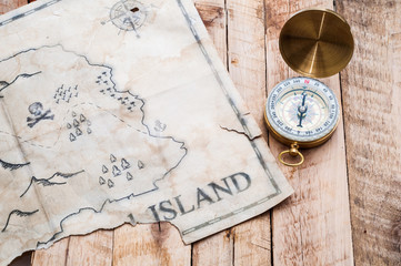Gold compass with retro and vintage map of fake island with Pirates treasure chest