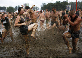 Revellers dance in mud-water during the 17th Woodstock Festival in Kostrzyn-upon-Odra Rive