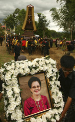 Family members hold a portrait of Agnes Datu Sarungallo as others carry her coffin in the background during a Rambu Solo ceremony in Tana Toraja