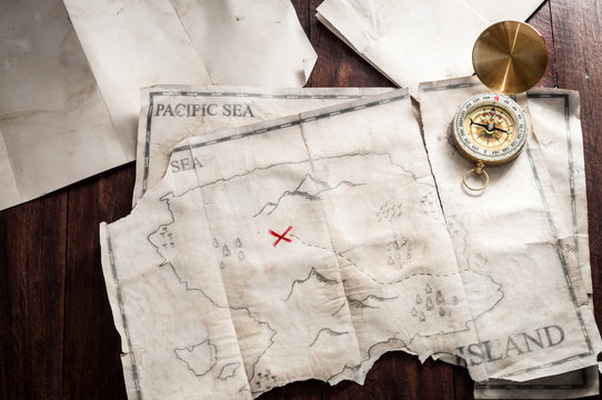 Table with vintage papers and old crumpled and folded map of fake Island with treasure chest.