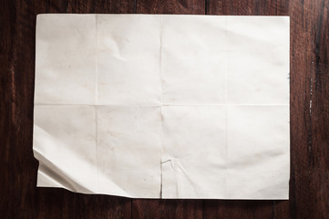 Vintage broken empty folded and crumpled paper on dark wooden table