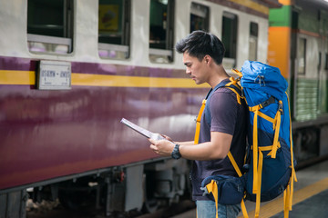 Traveler wearing backpack holding map on railway at train station