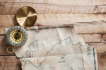 Top view to gold compass on wooden desk with fake handmade broken vintage map