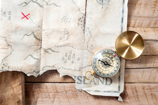 Nautical compass with fake treasure map of abstract island with red cross on wooden table