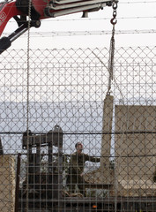 An Israeli soldier oversees the establishment of a new wall as seen from the village of Kefar Kela toward the Israeli border in southern Lebanon