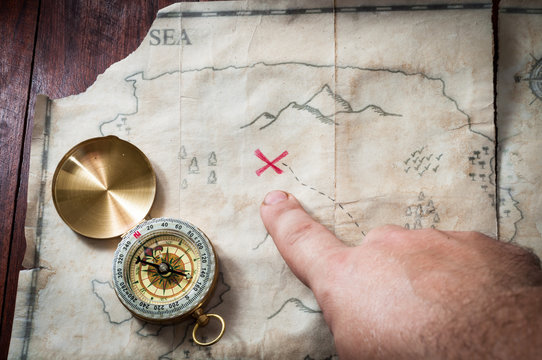 Man point with finger into red cross on Ancient Treasure fake map with gold compass on wooden desk
