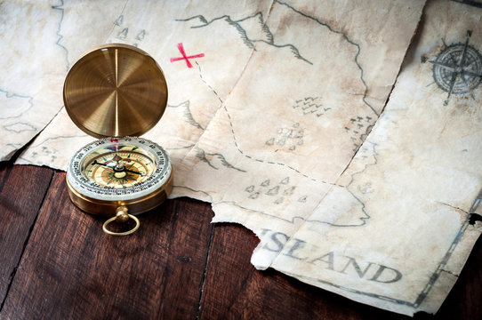 Gold nautical compass on old retro pirate map with red mark cross. Fake treasure map on wooden table