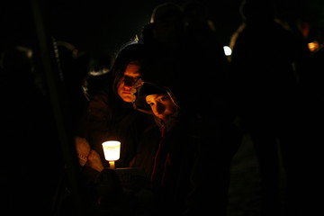 People take part in a candlelight vigil in Newtown
