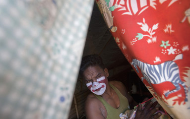 A clown looks out of his tent before a show at the Rambo Circus in Mumbai