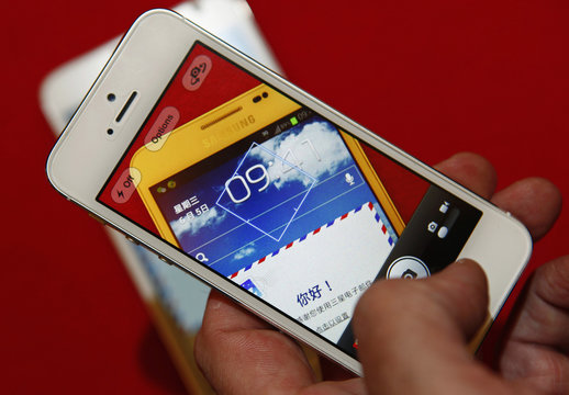A man uses an iPhone 5 to take a picture of a Samsung Galaxy Note smartphone in this photo illustration taken in Beijing