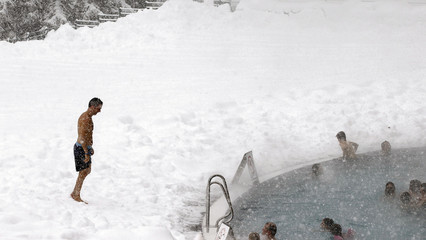 People relax in a public swimming pool during heavy snowfalls in Davos