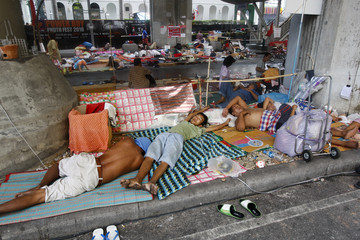 """Protesters sleep on the sidewalks of the barricaded anti-government """"red shirt"""" encampment in Bangkok's shopping district"""