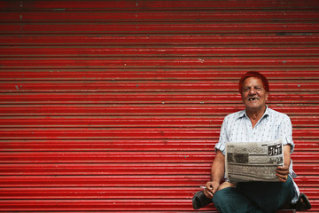 A man with his hair dyed red reads a newspaper with news about elections in front of red doors in the old part of Lahore