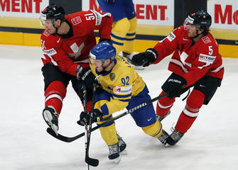 Sweden's Landeskog fights for the puck with Switzerland's Blindenbacher and Gardner during their 2013 IIHF Ice Hockey World Championship final match at the Globe Arena in Stockholm