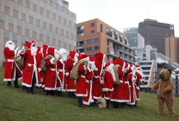People dressed in Santa Claus and fairy costumes pose for pictures after annual meeting of rent-a-Santa Claus service in Berlin
