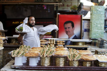 A vendor sells traditional sweets near a picture of President Assad during Ramadan in Damascus, Syria