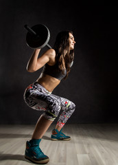 Sporty sexy girl with barbell on a dark background. Athlete doing exercises in the gym
