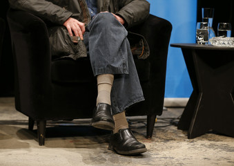 The shoes and socks of Houellebecq are seen as the French author sits on stage for a reading with German actor Doelle (not pictured) at the Schauspiel Koeln, the public theater of the western German city of Cologne