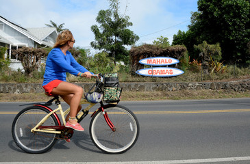 A woman rides her bike past a sign, thanking the Obamas, near the house where U.S. President Barack Obama and his family are staying during his Christmas holiday vacation in Kailua, Hawaii