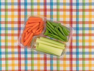 Veggies in a container on a colorful place mat top view.
