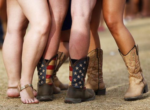 Man fan in cowboy boots in colours of U.S. flag is surrounded by girls during first day of Stagecoach country music festival in Indio