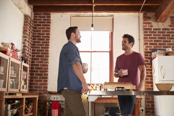 Two male friends hanging out in kitchen, low angle