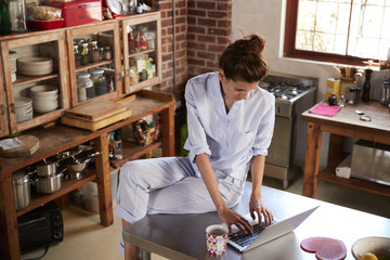 Woman in pyjamas sits using laptop in kitchen, high angle