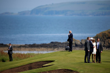 Secret Service agents keep watch as Eric Trump, Republican presidential candidate Donald Trump, Ivanka Trump and Donald Trump Jr pose for a photo following a news conference at Turnberry Golf course in Turnberry