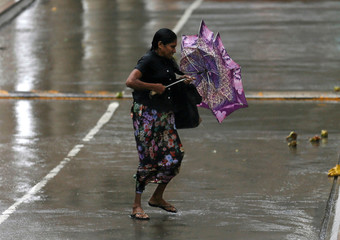 A woman stuggles to hold her umbrella from high wind and rain during a wet day in Colombo , Sri Lanka