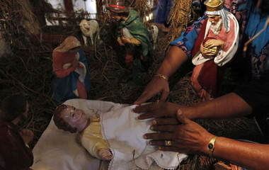 Devotees pray on a statue of baby Jesus at a church during a special mass on Christmas day in Colombo