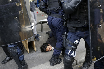 French riot police apprehend a man during clashes at a demonstration against plans to reform French labour laws in Paris