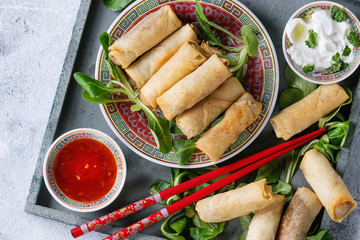 Fried spring rolls with red and white sauces, served in china plate on wood tray with fresh green salad and wooden chopsticks over gray blue texture background. Flat lay, close up. Asian food