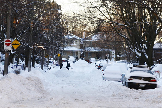 Residents use a shovel to remove snow from a road in a residential area after a snowstorm in Toronto, Ontario