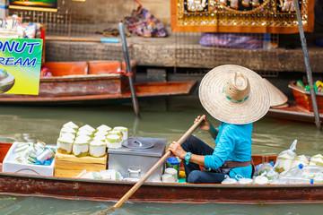 Local vendors selling goods at Damnoen Saduak Floating Market near Bangkok in Thailand, Damnoen Saduak is a very popular tourist attraction.