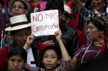 "A boy holds a sign which reads, ""No more corruption"", during a demonstration demanding the resignation of Guatemalan President Otto Perez Molina, in downtown Guatemala City"