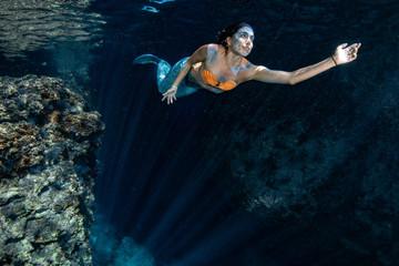 Mermaid swimming underwater in the deep blue sea