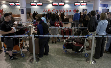 Air Canada travellers wait at the check-in area as baggage handlers at Pierre Elliott Trudeau airport walked off the job in Montreal