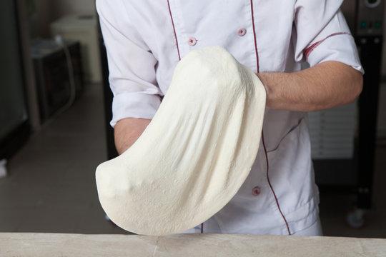 Male baker preparing pizza. pizza prepare. Cook making delicious pizza at the restaurant. making delivery pizza.