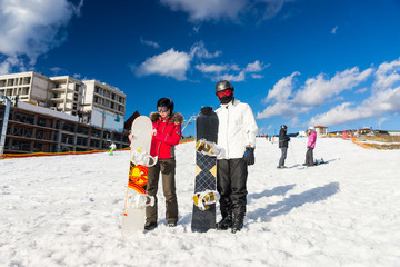 Young couple in ski suits, helmets and ski goggles standing with snowboards in a ski-resort