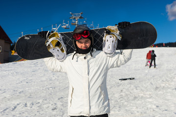 Young man in ski-suit standing and holding his snowboard on his shoulders