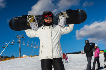 Young male in ski-suit standing and holding his snowboard on his shoulders