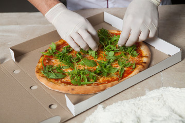 Male baker preparing pizza. pizza prepare. Cook making delicious pizza at the restaurant. making delivery pizza.