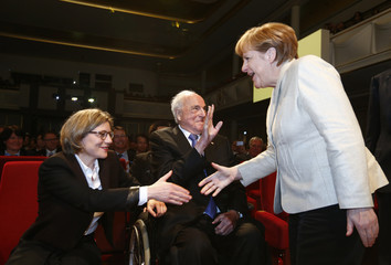 German Chancellor Merkel goes for a handshake with Maike Richter-Kohl, wife of former chancellor Kohl at an event marking the 150th anniversary of BASF company in Ludwigshafen