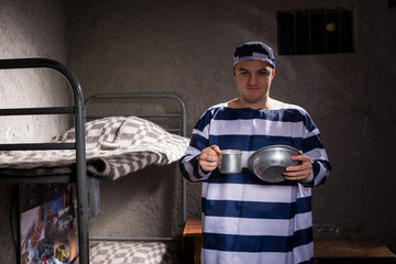 A male prisoner wearing prison uniform holding aluminum dishes in a prison cell