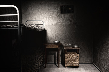 A dark empty prison cell with bunk bed and bedside table