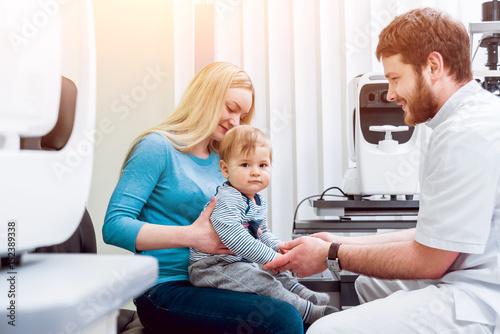 2b846866292 Basic eye examination. Mother holds child during eye exam.