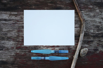White paper sheet and water brashes on the wooden table outdoors