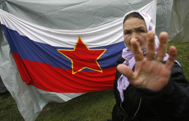 Bosnia Muslim woman gestures in front of a flag used by Slovenia, when it was still part of the former Yugoslavia, in Zenica