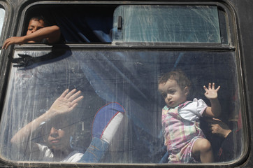 Palestinian children look out of bus window, in hopes of crossing into Egypt, at Rafah crossing between Egypt and southern Gaza Strip