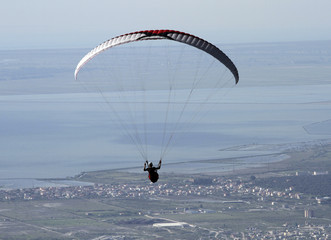 A paraglider flies during the annual Balkan paragliding competition over the city of Vlore